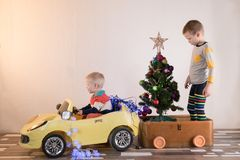 Funny little smiling kids driving toy car with Christmas tree. Happy child in colour fashion clothes bringing hewed xmas tree from. Snowy forest. Boys having stock photography