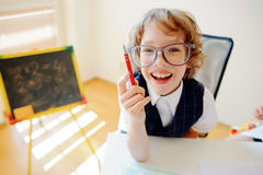 Funny little student bespectacled sits at school desk. It is a disciple of an elementary school. In a hand at boy ball pen. On a school desk copybooks lay Stock Image