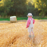 Funny little toddler boy in leather shors, walking  through whea Royalty Free Stock Photo
