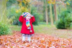 Funny little toddler girl playing in autumn park Stock Photo
