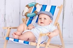 Funny little toddler sitting on the deckchair. Cute studio portrait of adorable baby boy Royalty Free Stock Photo