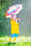 Funny little toddler with umbrella playing in the rain. Funny cute curly toddler girl wearing yellow waterproof coat and boots holding colorful umbrella playing Stock Photography