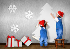 Funny Little twins dressed Santa hat, glue Christmas tree on wal Stock Photo