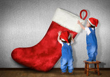 Funny Little twins dressed Santa hat, hangs big Christmas stocki Royalty Free Stock Photos