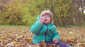 Funny smiling 1 year old boy Walking in the autumn Park at the Sunset with bread in hand . Happy Childhood Concept. Slow stock footage