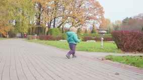 Funny smiling 1 year old boy Walking in the Park at the Sunset with bread in hand . Happy Childhood Concept. Slow motion. Funny Little 1 year old boy Walking in stock video