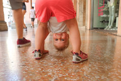Funny look. A funny baby girl looks around having head upside down Stock Images