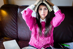 Funny looking brunette woman student trying to study in her room. Funny process of studying for exams stock photos