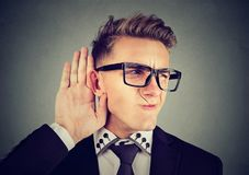 Funny looking displeased man eavesdropping listing into private conversation Stock Photography