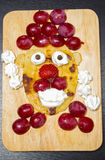 Funny looking face made of sliced grapes, strawberries and pancake, as seen from above Stock Image