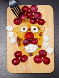 Funny looking face made of sliced grapes, strawberries and pancake, as seen from above Royalty Free Stock Images