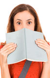 Funny looking female student behind her book Royalty Free Stock Images