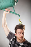 Funny looking guy with dandelions on his head. Funny looking guy with a sprinkler and dandelions growing from his red hair Stock Photo