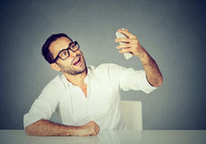 Funny looking man taking pictures of him self with smart phone Stock Image