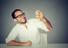 Funny looking man taking pictures of him self with smart phone Stock Images