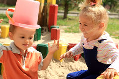 Funny lovely kids. Portrait of the two funny lovely kids playing in the sandbox Stock Photos