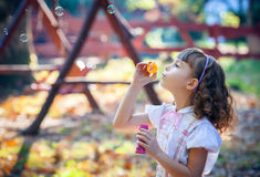 Funny lovely little girl blowing soap bubble Stock Photo
