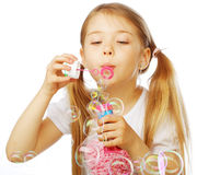Funny lovely little girl blowing soap bubbles Stock Photo