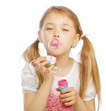 Funny lovely little girl blowing soap bubbles Royalty Free Stock Images