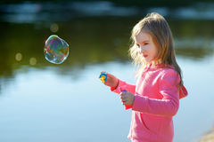 Funny lovely little girl blowing soap bubbles Stock Images