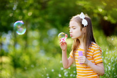 Funny lovely little girl blowing soap bubbles on a sunset outdors stock photography