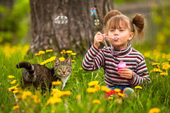 Funny lovely little girl and a cat. Blowing soap bubbles Royalty Free Stock Photography