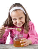 funny lovely little girl eat honey Stock Photography