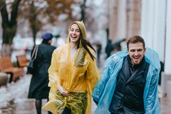 Funny and loving guy and girl in yellow and blue raincoats are running in the rain outside. stock photography