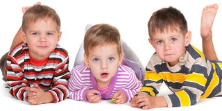 Funny lying kids in striped shirts Stock Photos