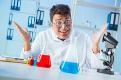 The funny mad chemist working in a laboratory. Funny mad chemist working in a laboratory Royalty Free Stock Images