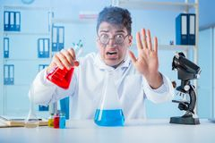 The funny mad chemist working in a laboratory. Funny mad chemist working in a laboratory Stock Photography