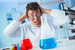 The funny mad chemist working in a laboratory. Funny mad chemist working in a laboratory Stock Image