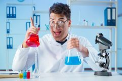 The funny mad chemist working in a laboratory. Funny mad chemist working in a laboratory Royalty Free Stock Photo