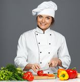 Funny mad woman cook. Funny mad young woman cook cutting fresh tomatoes Royalty Free Stock Photography