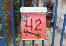 Funny mail box. Funny red mail box with number 42 on a blue fence Stock Images