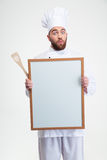 Funny male chef cook holding blank board. Portrait of a funny male chef cook holding blank board isolated on a white background Stock Photos