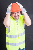 Funny male constructor forgot to do something. Funny male constructor forgot to do or remember something isolated on black background stock photo
