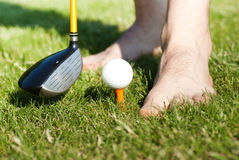 Funny male feets playing with golf ball Stock Photo