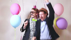 Funny male friends dancing with props. Two funny male friends dancing with props in photo booth stock footage