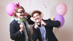 Funny male friends dancing with props. Two funny male friends dancing with props in photo booth stock video