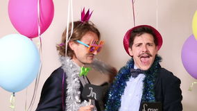 Funny male friends dancing with a sign in love in photo booth. Funny young male friends dancing with a sign in love in photo booth stock footage