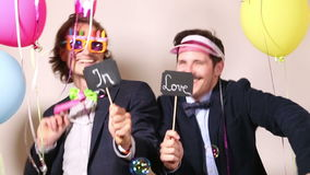 Funny male friends dancing with a sign in love in photo booth. Funny young male friends dancing with a sign in love in photo booth stock video
