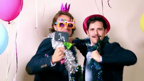 Funny male friends dancing with a sign in love in photo booth. Funny young male friends dancing with a sign in love in photo booth, graded stock footage
