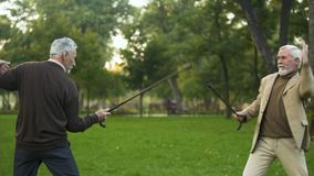Funny male friends fighting with walking sticks in park, pretending be knights
