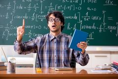 The funny male math teacher in the classroom. Funny male math teacher in the classroom royalty free stock images