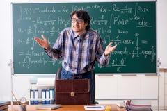 The funny male math teacher in the classroom. Funny male math teacher in the classroom royalty free stock photos