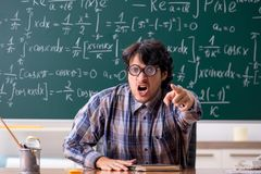 The funny male math teacher in the classroom. Funny male math teacher in the classroom stock image