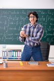 The funny male math teacher in the classroom. Funny male math teacher in the classroom stock photography