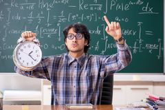 The funny male math teacher in the classroom. Funny male math teacher in the classroom stock images