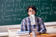 The funny male math teacher in the classroom. Funny male math teacher in the classroom stock photo